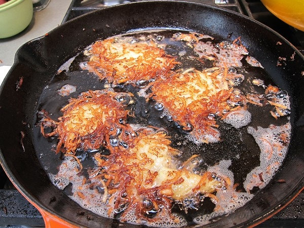 Potato pancakes frying in heavy pan