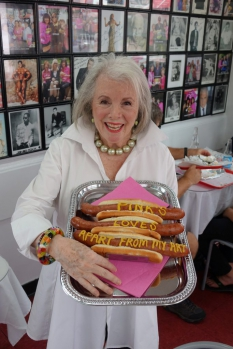 Sandra holding a silver tray of hot dogs with the words